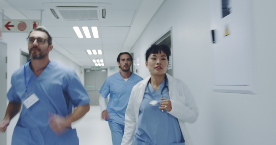 Reverse tracking shot of young Asian female doctor and male interns running through hospital corridor responding to an emergency. Healthcare workers in the Coronavirus Covid19 pandemic