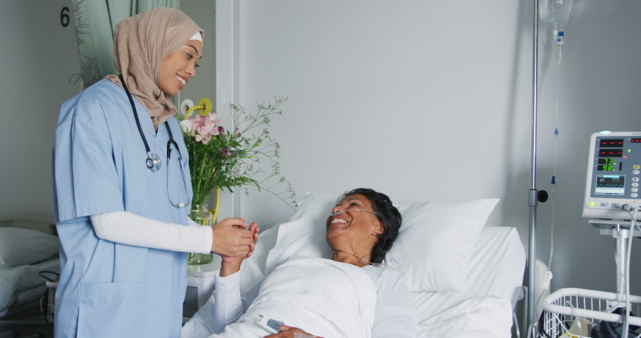Close up shot of young mixed race female doctor wearing hijab comforting a senior mixed race female patient lying in hospital bed. Healthcare workers in the Coronavirus Covid19 pandemic