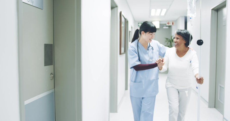 Reverse tracking shot of young Asian female doctor supporting a senior mixed race female patient while she walks in a hospital corridor. Healthcare workers in the Coronavirus Covid19 pandemic