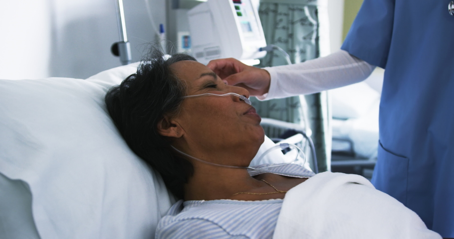 Mid section of young mixed race female healthcare worker comforting senior mixed race female patient lying in a hospital bed. Healthcare workers in the Coronavirus Covid19 pandemic