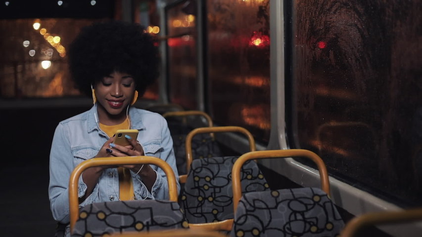 Attractive young african american woman using smartphone riding at public transport and looking out the window. Night time. City lights background. | Shutterstock HD Video #1033268882