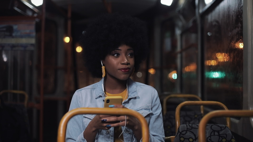 Attractive young african american woman using smartphone riding at public transport and looking out the window. Night time. City lights background. | Shutterstock HD Video #1033268930
