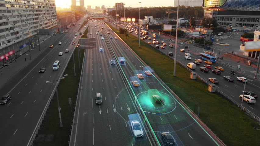 Beautiful aerial view to autonomous cars self-driving on the highway in Moscow. Picturesque aerial panorama of the road traffic in a big city on the sunset.