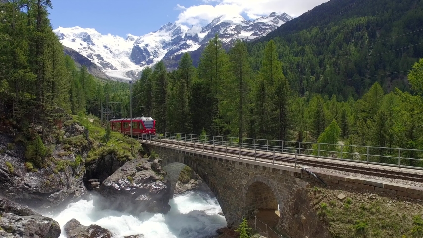 Bernina Express, red train of Bernina and glacier of Morteratsch in the Swiss Alps. Unesco World Heritage