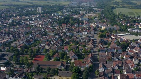 Aerial of the city Kirchheim unter Teck in Germany.  Camera pans left and then rotates right, tilting slightly down.