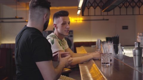 Two adult men sitting at the bar counter, third guy joining the company, mates hugging and giving high five. Relaxed male friends chilling together drinking elite alcohol. Day off