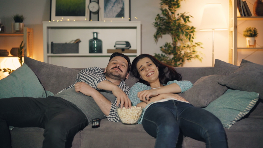 Happy young people man and woman are watching TV laughing and eating popcorn lying on couch at home enjoying leisure time and entertainment in apartment.