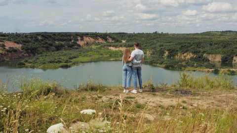 Couple is standing on a mountain cliff by the lake. Couple in love hugging against the background of beautiful views of nature. Aerial. 4K