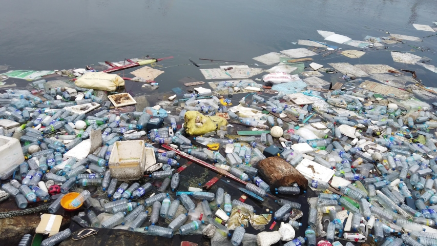 Plastic pollution trash in ocean with different kinds of garbage - plastic bottles, bags, wastes floating in water. Sea ocean water pollution concept. Plastic pollution crisis