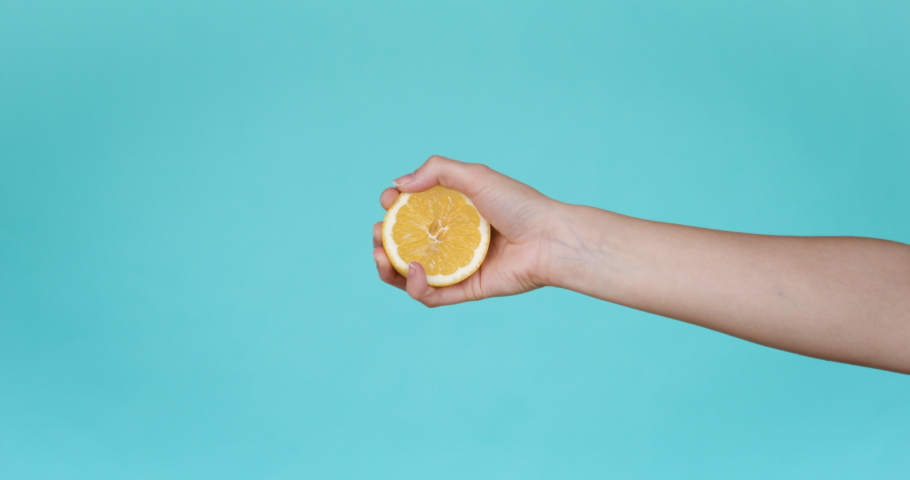Squeeze juice from lemon, hand squeezes half yellow lemon. Close-up. Slow motion. Turquoise background.
