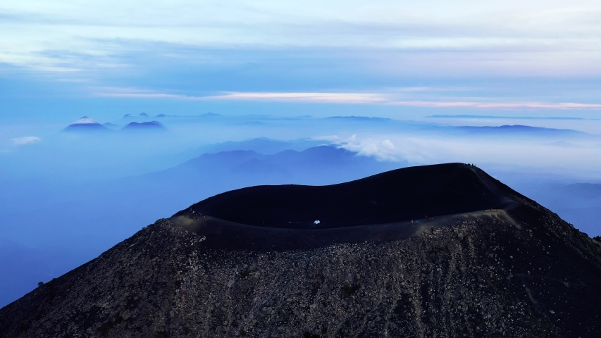 Guatemala volcano Acatenango and volcano Fuego aerial drone 4K video. Fly over Acatenango volcano crater where hikers are watching beautiful sunrise scenery. Aerial landscape panorama shot.