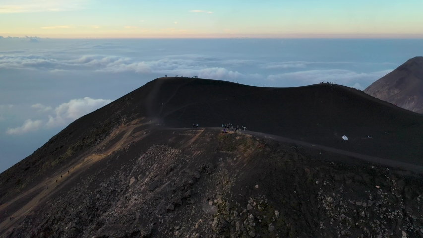 Guatemala volcano Acatenango and volcano Fuego aerial drone 4K video. Hikers walking to the top of the mountain during beautiful sunrise. Amazing hiking trail and tourism destination in Guatemala. | Shutterstock HD Video #1033350869