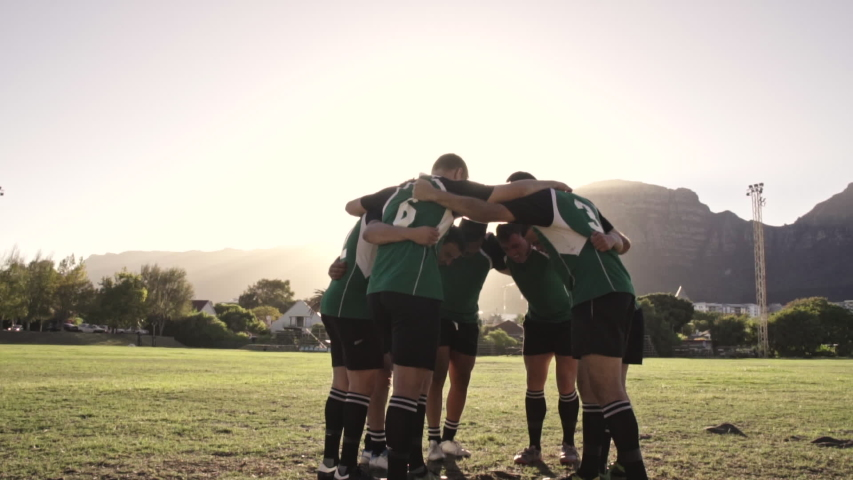 Group of rugby players performing a war cry before the match. Rugby team standing in a huddle doing their war cry.