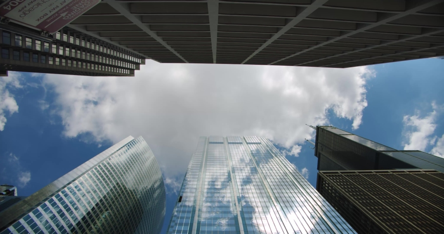 Looking up at skyscrapers business buildings in dowmtown, clouds rolling in sky and reflections on glass | Shutterstock HD Video #1033366610