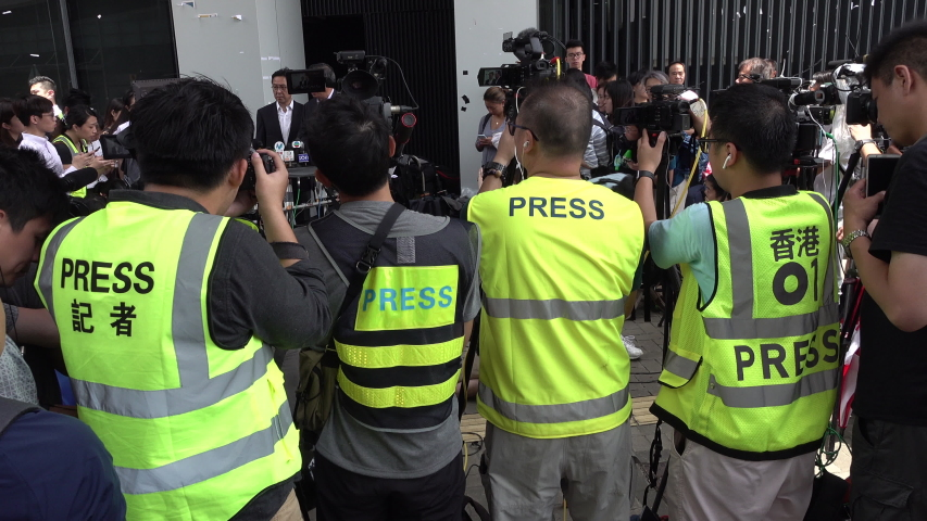HONG KONG - 2 JULY 2019: Asian journalists wear press outfits during statement of Andrew Leung, President of the Hong Kong Legislative Council, after it was damaged and attacked by protesters