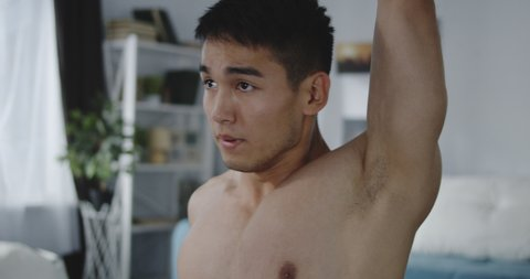 Medium close-up of a young man warming up before training at home