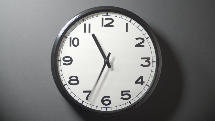 Closeup of White Clock Face in timelapse in daytime of office dark grey wall  | Shutterstock HD Video #1033388930