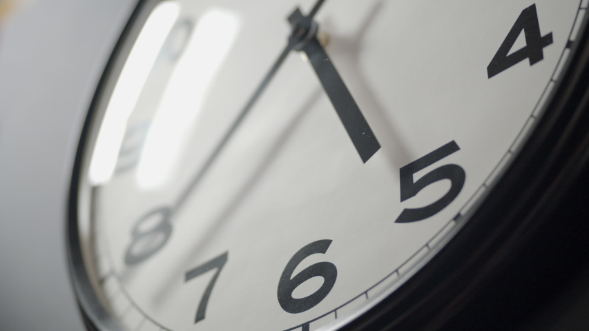 Closeup of White Clock Face in timelapse in daytime of office dark grey wall