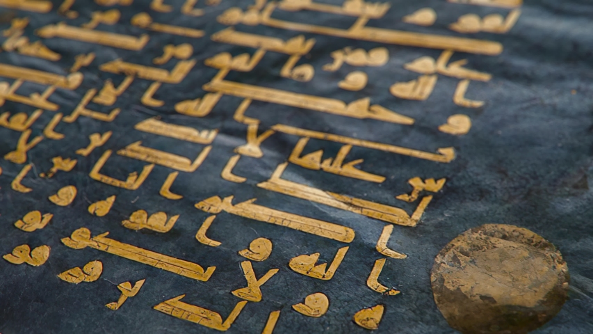 "The Blue Qur'an manuscript in Kufic calligraphy written in gold, shallow depth of field close-up slow tilt up CGI shot. Translates to ""In The Name of Allah, The Most Beneficent, The Most Merciful"" 