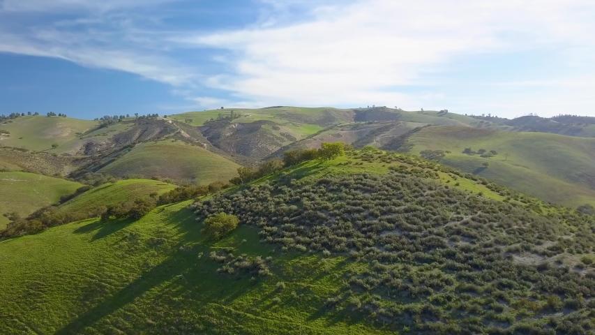 Incredible aerial drone shot of green landscape across the mountains near San Antonio lake, Monterey County, California