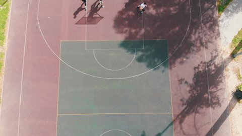 Young fit men playing basketball on the court in the street