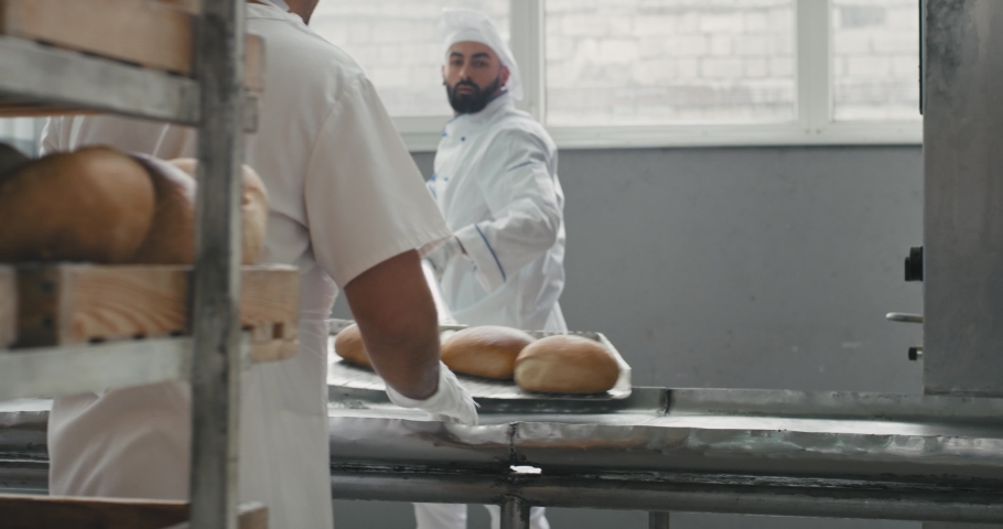 Hard day working process of unloaded the bread from oven machine on the special shelves in a bakery factory | Shutterstock HD Video #1033408991