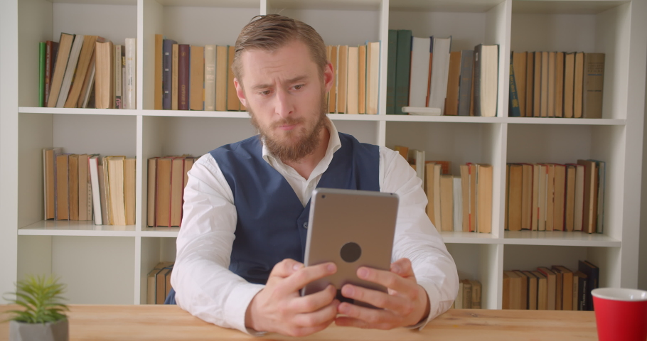 Closeup portrait of young caucasian businessman having a video call on the tablet on the workplace indoors with bookshelves on the background