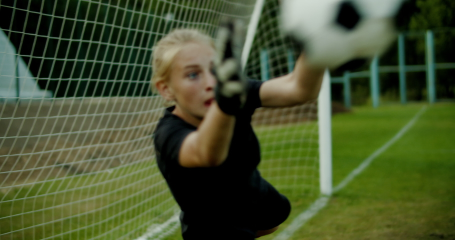 Young teenager girl soccer goalie diving to catch the ball during a match or practice. 4K UHD