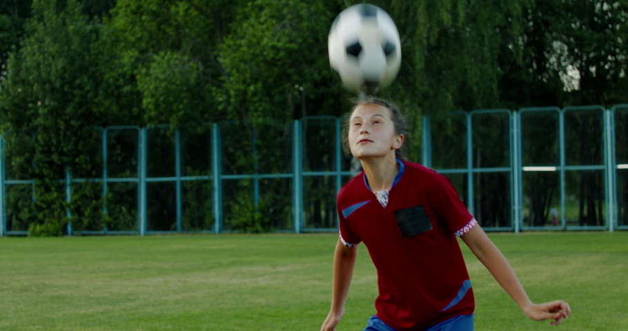 Young Caucasian teenager girl soccer football players heading the ball during practice session. 4K UHD
