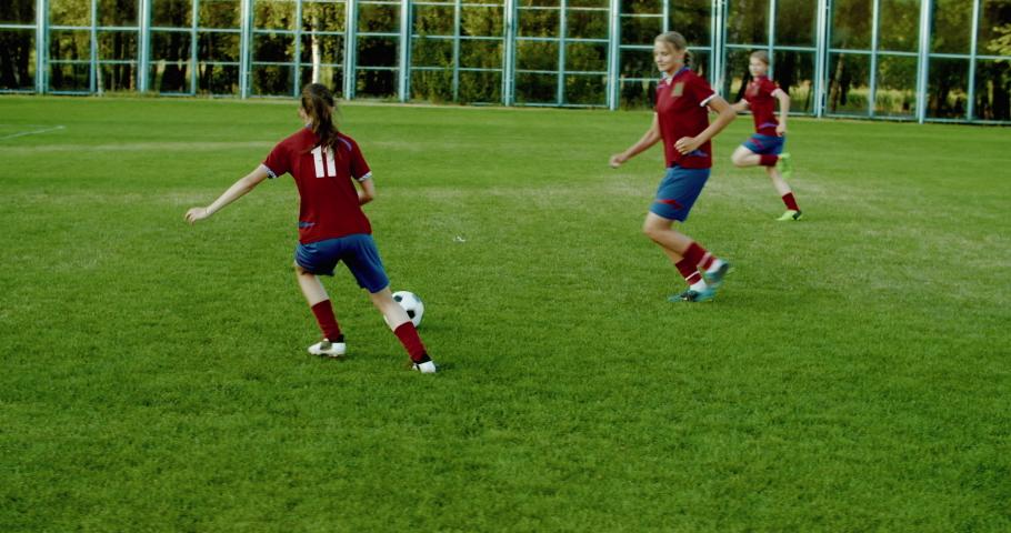 TRACKING Caucasian teenager girl soccer football team scoring a goal against opposing team. 4K UHD 60 FPS SLOW MOTION | Shutterstock HD Video #1033417292