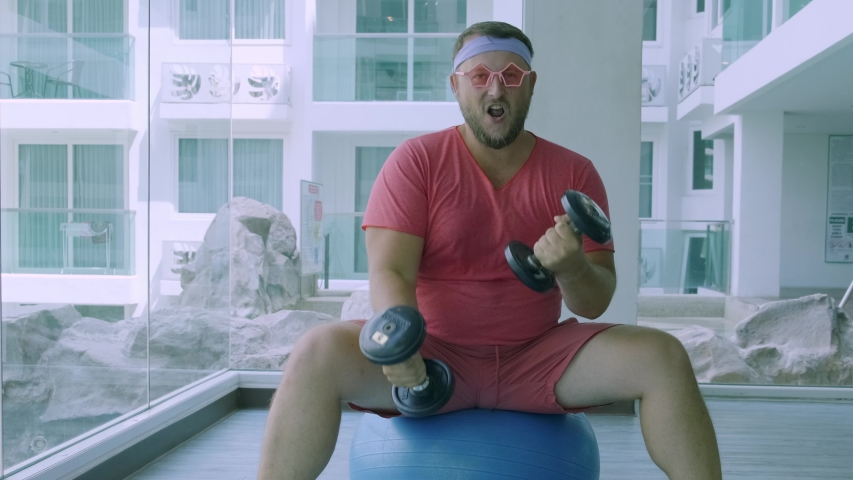 Playful fat man in a pink T-shirt and pink glasses is engaged in fitness with dumbbells and a fit ball in the gym.