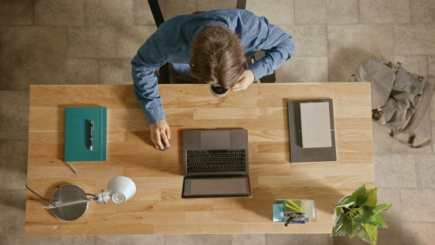 Top View Zoom Out Shot: In the Office Businessman Sitting at the Wooden Desk Opens Laptop and Starts Working He Drinks Coffee, Types, Writes Emails, Surfs the Internet, Designs Software Royalty-Free Stock Footage #1033427462