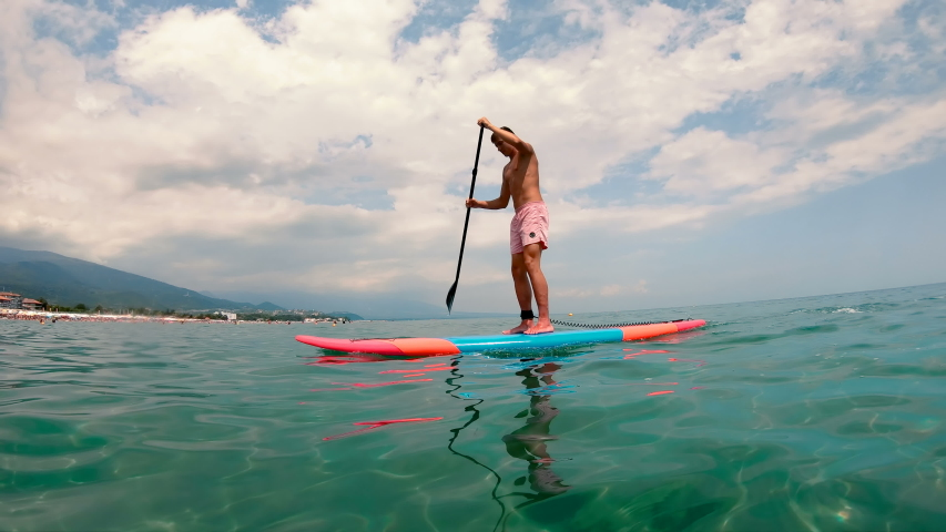 Chalkiness, Greece - 08 July, 2018: Paddle boarding, surfing in the sea with crystal clear water | Shutterstock HD Video #1033437122