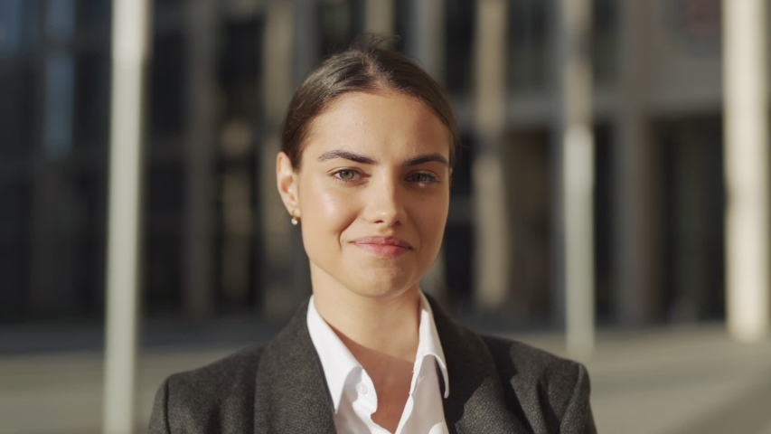 Head and shoulders slow motion portrait of beautiful and confident young woman in formal suit standing outdoors, looking at camera and smiling  Royalty-Free Stock Footage #1033442102