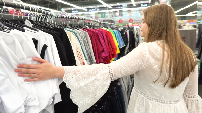 Close up of a girl goes through clothes dresses summer outfit, T-shirts and shirts and shop the boutique, the supermarket on the rack, close-up of hands and racks of clothes, shopping  | Shutterstock HD Video #1033444091