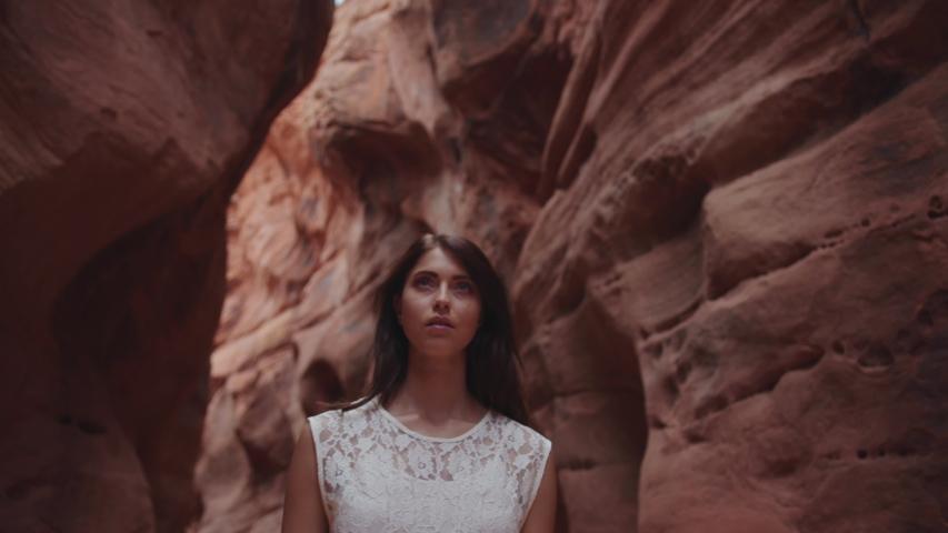 Female fashion model in white dress walking between red rocks of Grand Canyon   Shutterstock HD Video #1033450631