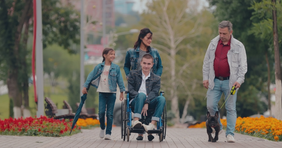 Disabled guy walks with the family in the park. Young man in a wheelchair rides along a path in a public garden. | Shutterstock HD Video #1033460717