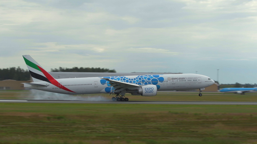 Oslo airport norway - ca july 2019: huge airplane emirates boeing 777 blue expo 2020 logo landing runway panning right