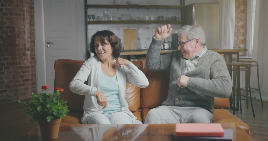 Happy senior couple sits on sofa. Aged caucasian woman and man start to do various movements to the rhythm of song and have fun Royalty-Free Stock Footage #1033469807