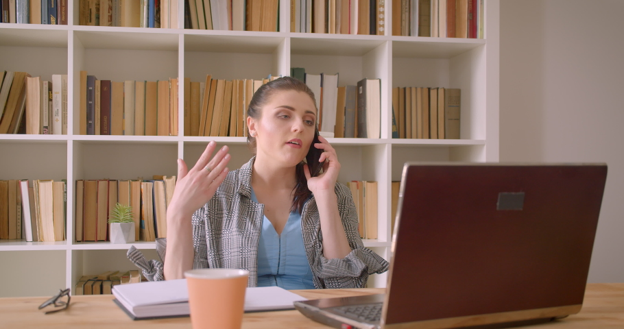 Closeup shoot of young caucasian businesswoman using the laptop and having a phone call in the library office indoors | Shutterstock HD Video #1033470731