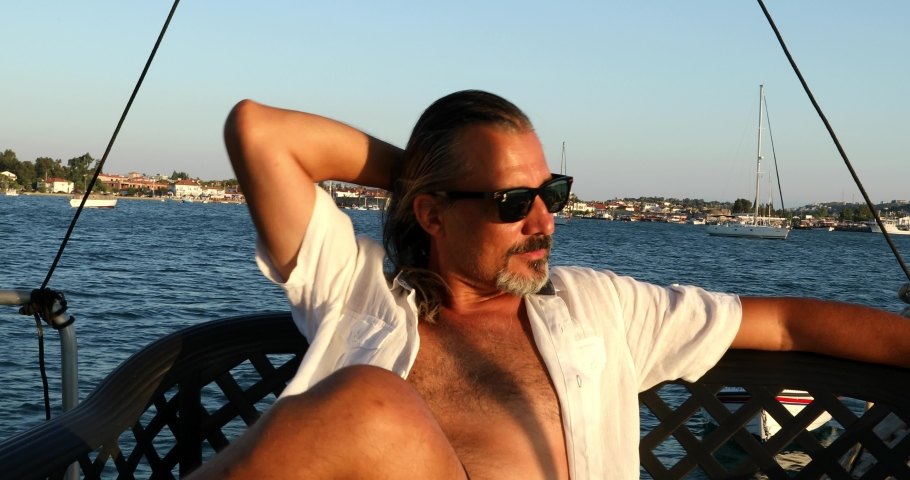 Portrait of a middle aged burunette man on luxury yacht resting at summer holiday | Shutterstock HD Video #1033478420