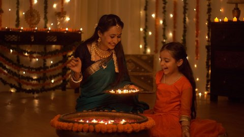 Beautiful Indian mother and daughter celebrating the Indian festival - Diwali Concept. Mother and daughter decorating their house together. Beautifully decorated house with candles, lights, and flo...