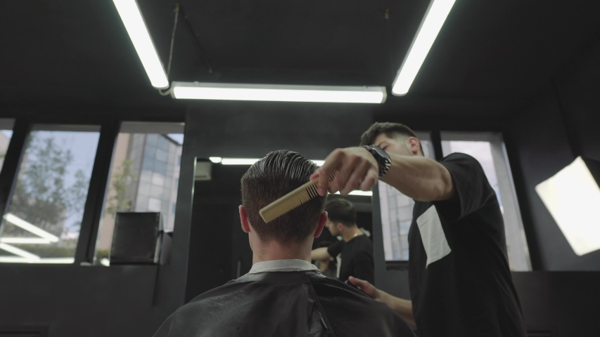 Attractive male is getting a modern haircut in barber shop. Barber wets hair by spray and combs them. Handheld shot. 4K.