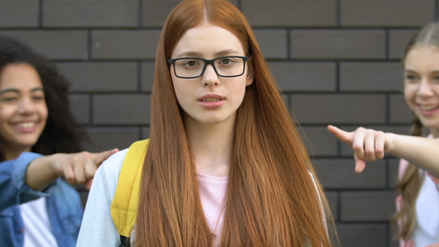 Teenagers pointing at red hair girl in glasses, mocking nerd, verbal bullying