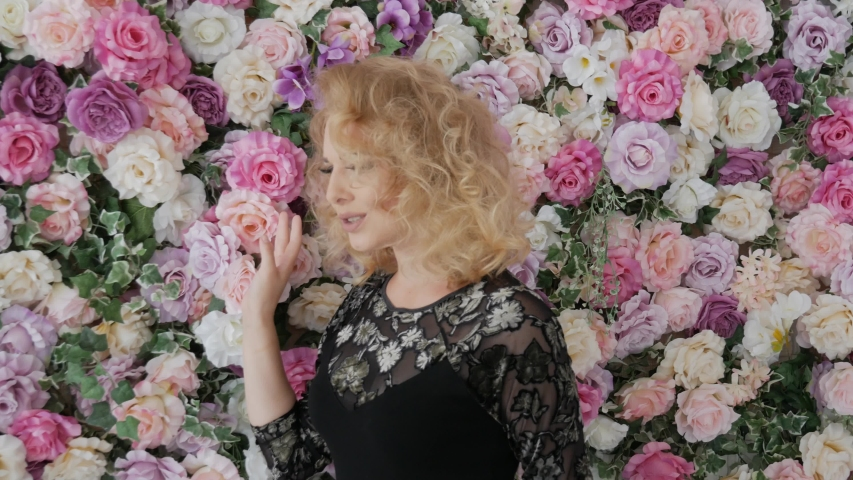 Singer young woman walks along flowers and sings. Elegant curly blonde sings flowers near the wall. Girl in a black evening dress with flowers