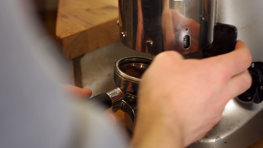 Close-up Barista pours ground coffee in portafilter. Close-up of barista grinding coffee. Man bartender in the workplace. Man makes coffee using coffee machine. | Shutterstock HD Video #1033509323