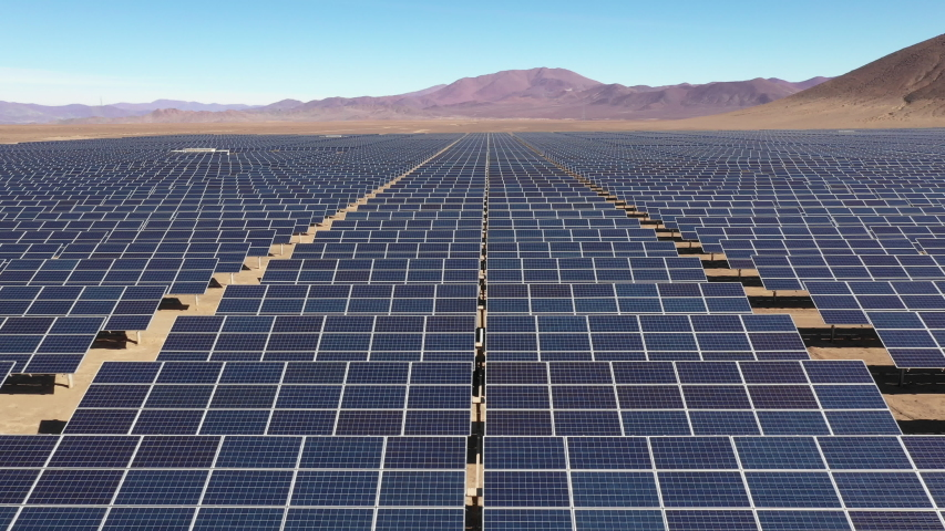 Aerial footage of hundreds solar energy modules or panels rows along the dry lands at Atacama Desert, Chile. Huge Photovoltaic PV Plant in the middle of the desert from an aerial drone point of view  | Shutterstock HD Video #1033511822