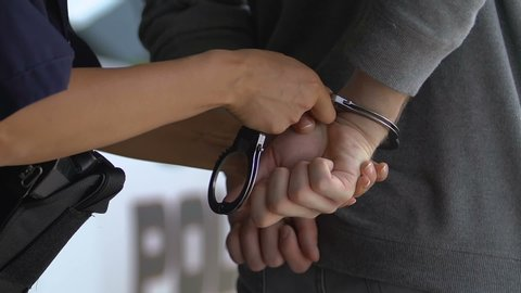 Brave policewoman arresting extremely dangerous criminal, putting handcuffs