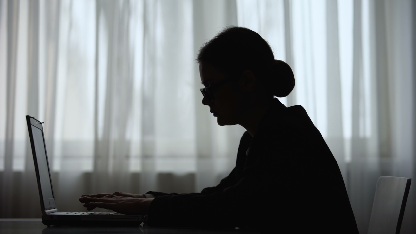 Shadow of woman reading message on her smartphone working on laptop, freelancer