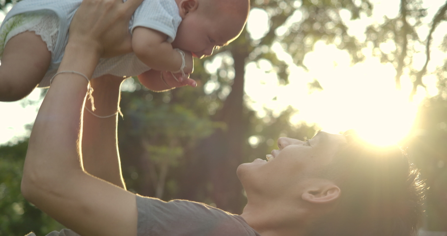 Father playing with baby at park. Young asian father holding his baby son aloft in park or garden with happy emotion. Slow motion.   Shutterstock HD Video #1033528373